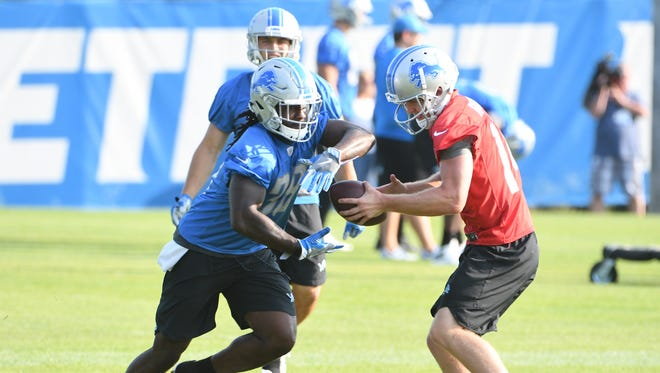Running back Tion Green fakes the handoff from quarterback Jake Rudock during Wednesday's training camp practice.