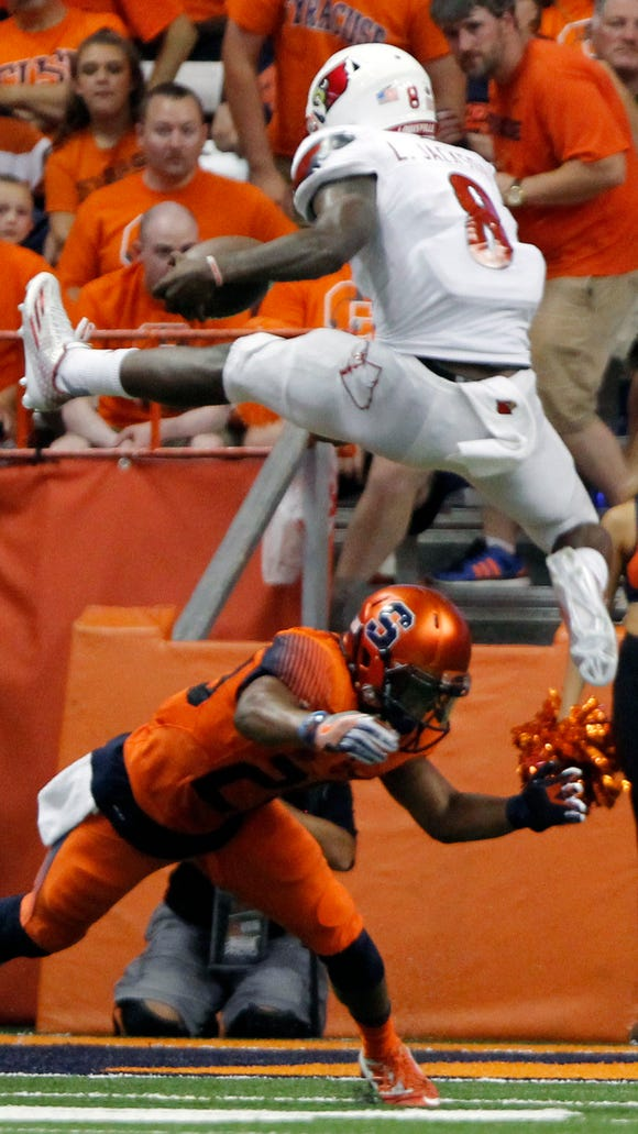 Louisville's Lamar Jackson jumps over Syracuse's Cordell Hudson and scores a touchdown in the first half of an NCAA college football game in Syracuse, N.Y., Friday, Sept. 9, 2016. (AP Photo/Nick Lisi)