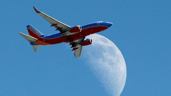 A Southwest Air flight crosses over a crescent moon as it passes over Whittier, Calif., en route to Los Angeles on Labor Day, Monday, Sept. 1, 2014.