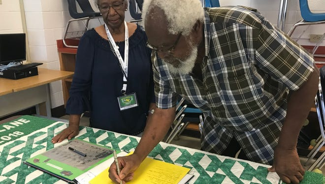 """Zella Woodruff, left, looks on as keynote speaker Lonnie Fitzgerald, Woodson High School Class of 1952, signs in to the all-class reunion for Woodson High School Friday. Fitzgerald also signed the quilt below the binder, taking his place on """"Memory Lane,"""" the name of the quilt."""