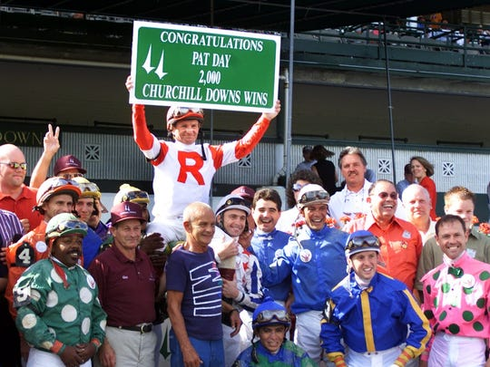 Pat Day held up a sign given to him by Churchill Downs as he posed with fellow jockeys for a photo after he rode Ruby Secret to his 2,000th win on June 30, 2000, at Churchill Downs.