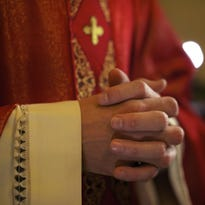 Catholic priest on altar praying during mass.
