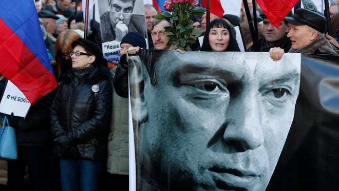 Russians participate with flowers and portraits in a memorial march for Boris Nemtsov to mark the first anniversary of his murder in Mocow on Feb. 27, 2016.