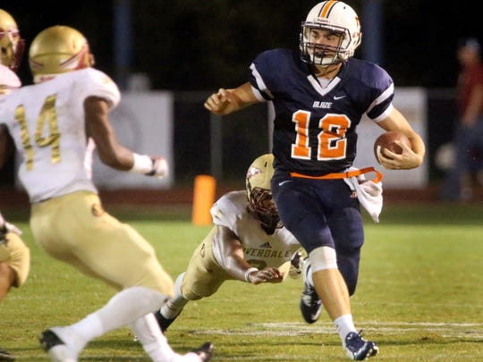Blackman's quaterback Miller Armstrong (12) runs the ball as Riverdale's Canaan Owens dives toward Armstrong and Riverdale's Preston Barge (14) moves in for a tackle, at the game at Blackman, on Friday Sept. 4, 2015.