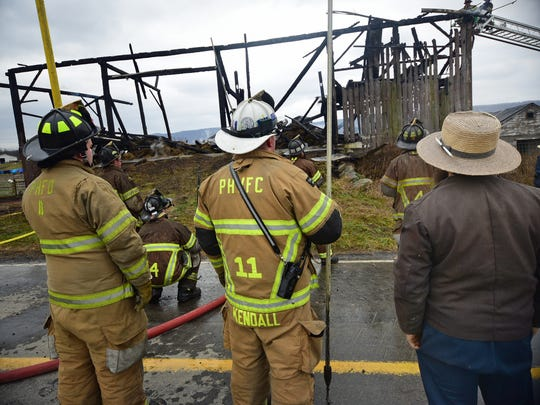 Firefighters work the scene during a fire Friday, Dec. 18, 2015 at the Ben Hostetler barn at 21348 Back Road, Doylesburg.