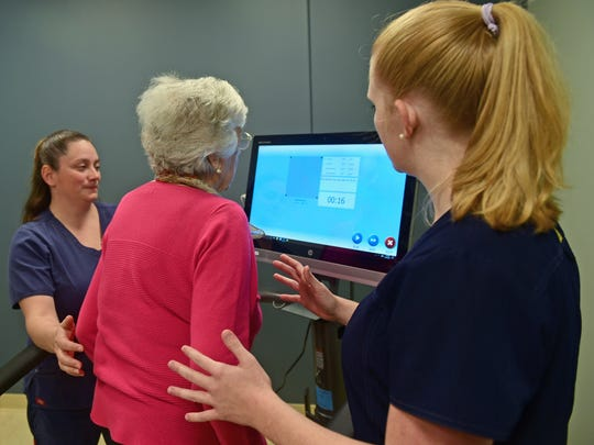 Christy Lautenslager, left, director of rehabilitation, and Paige Wright, physical therapy assistant, help Jo Ennis, center, as she uses a balance exercise machine on Tuesday, Oct. 10, 2017 at Shook Home Nursing and Rehabilitation Center. Several nursing homes in the area are opening separate or renaming themselves nursing and rehabilitation centers.