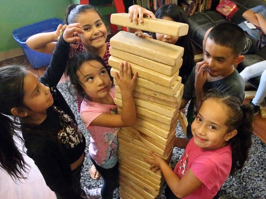 Ahtziri Gamez, bottom right, and other children enrolled in the Boys & Girls Clubs of El Paso's summer camp, stacked blocks high in an activity room at the club's headquarters at 801 S. Florence St. last year.