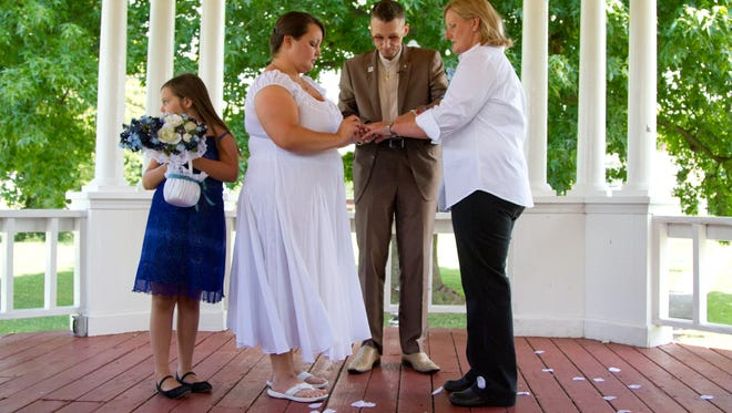 Sarah Peacock, of Louisville, Ky, puts a ring on Kristy Sturgill's, of Bardstown, Ky, finger alongside her daughter Lanie Peacock and Rev. Bojangles Blanchard during their wedding ceremony at Washington Park in Metropolis, Il. After being denied to apply for their marriage license at  the Jefferson Co. Clerk's Office in Louisville, Ky, the couple drove over two hundred miles to Metropolis, Il, to get married.  July 28, 2014.