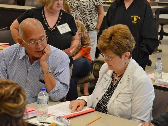 Literacy education trainer Ron Yoshimoto, left, discusses