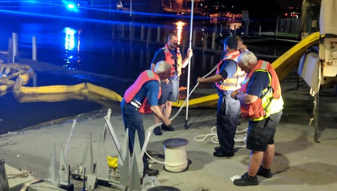 Members of the St. Clair County Dive Team Auxiliary and the Port Huron Fire Department deploy floating boom Friday to contain petroleum spilling from a tank at the Chicory Warehouse.