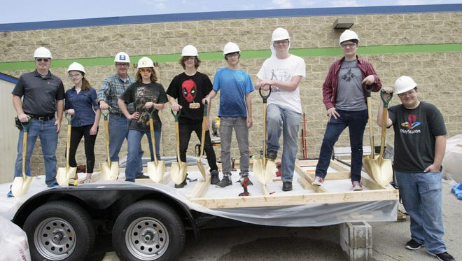 "From left: teacher Tim Pasche, Hannah Staats, Habitat Executive Director Jon Hoffman, Miranda Kelm, Sebastian Soerens, Will Zillmer, Zachary Krolow, Cade Byrand and Paxton Allison hold a mini ""trailer breaking"" ceremony for the IDEAS Academy portable shelter project that will be donated to a homeless veteran in Racine."