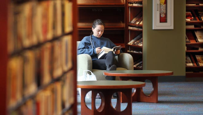 Megan Radenhauser, of Edgewood, reads a book in the Erlanger branch of the Kenton County Public Library. The Kentucky Court of Appeals reversed a decision that Campbell and Kenton County libraries had imporperly raised taxes.