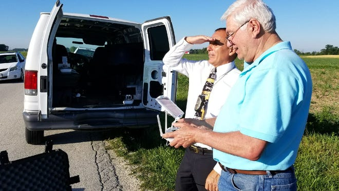 Bruce Chambers, right, owner of the Drone Store, assists Fremont Police Detective Roger Oddo at the scene in searching for a fugitive in Sandusky County.