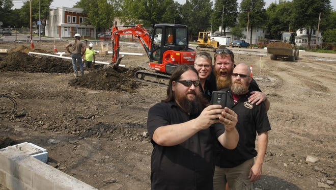 The owners of Three Heads Brewing take a selfie on the site of their new brewery under construction at 186 Atlantic Ave in the city.