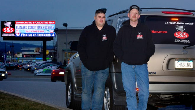 Brad Sweitzer Sr., left, and Phil Schussler of S&S Storm Chasing and Forecasting Team, are busy tracking the coming snow storm and updating York via an electronic billboard along Route 30 near Roosevelt Ave., Wednesday January 20, 2016.