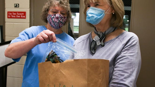 Renee Rimer, left, and Linda Blalock prepare bags with supplies, including face masks, for students returning to school at St. Mark United Methodist Church in Northport on Saturday, Aug. 15, 2020. The drive-thru back-school supplies giveaway benefited clients of the church's food pantry.