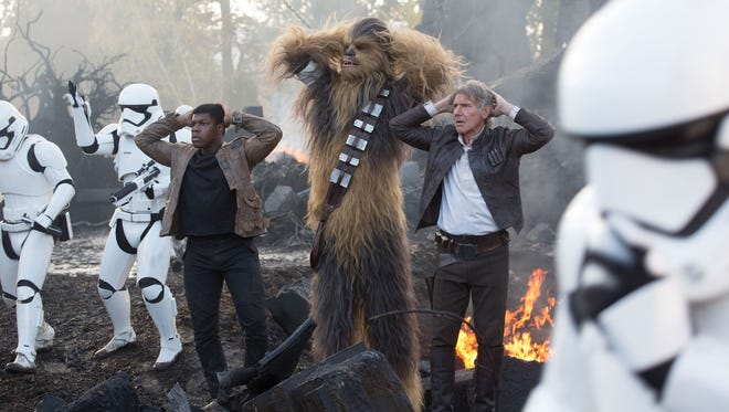 Finn (John Boyega), joins Chewbacca (Peter Mayhew) and Han Solo (Harrison Ford) in 'Star Wars: The Force Awakens.'