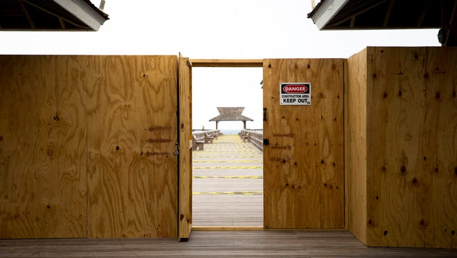 A temporary plywood wall prohibits the public from walking on the second half of the Naples Pier on Sept. 21, 2017.
