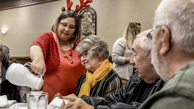 Janene Radke refills a patron's coffee cup during the Kansas Children Service League's 2019 Red Stocking Breakfast at the Clarion Inn Convention Center. Due to the COVID-19 pandemic, KCSL is changing the event to a virtual one this year.
