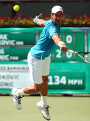 Novak Djokovic of Serbia leaps to return a ball to Milos Raonic of Canada on his way to a third straight and fifth total BNP Paribas Open title Sunday, March 20, 2016, in Indian Wells, Calif. Djokovic won in straight sets, 6-2, 6-0.
