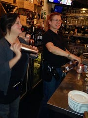 Bartender and server Lori Horton (left) prepares a martini, while bartender Maddy Freeman pours wine.