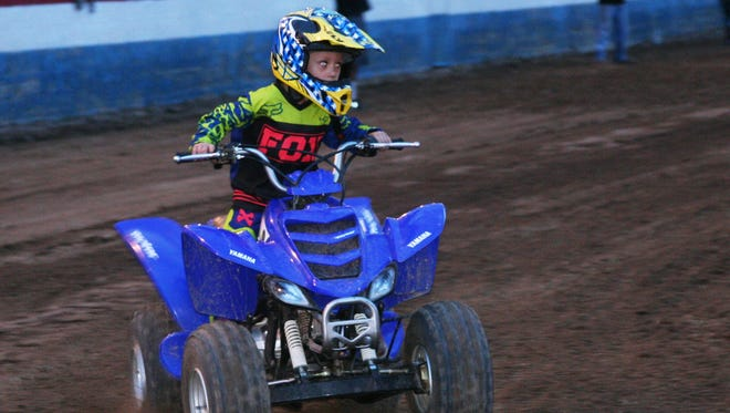 Young quad rider Barrett Stone rounds a turn during the flat track racing Monday night in the Fairgrounds arena, kicking off the 2014 Lyon County Fair and Rodeo.