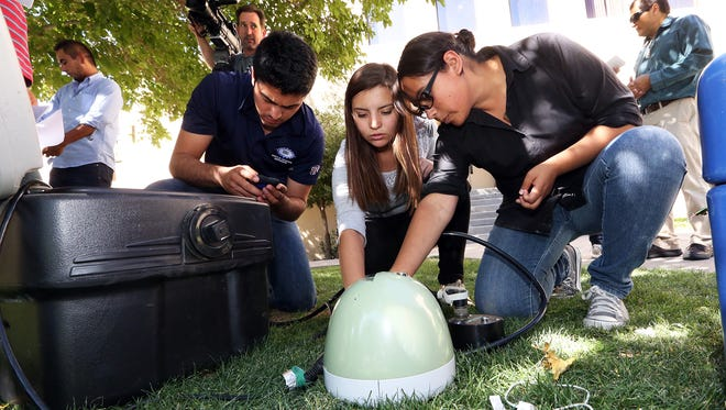 Jaqueline Ochoa, right, and fellow geoscience engineering student Laura Molina of the Autonomous University of Ciudad Juarez, check ground sensing equipment with UTEP doctoral student Solymar Ayala Cortez outside the Geological Sciences Building at UTEP Monday. A group from both universities will travel to Mexico City and the Mexican state of Chiapas to record seismic activity.