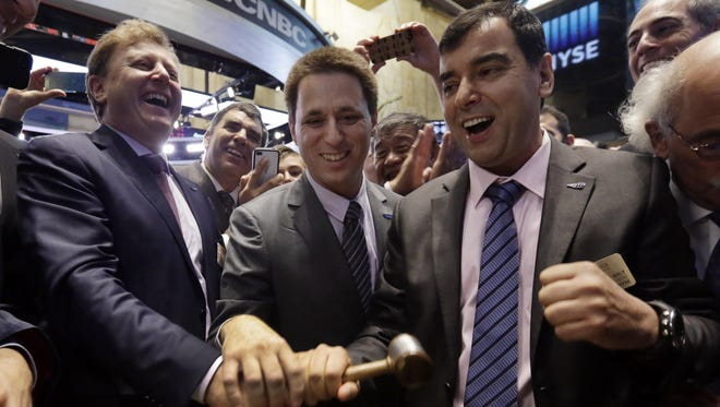 Mobileye President & CEO Ziv Aviramon, left, CFO Ofer Maharshak, center, and Chairman Amnon Shashua, clasp hands to ring a ceremonial bell as their company's IPO begins trading, on the floor of the New York Stock Exchange Friday, Aug. 1, 2014.