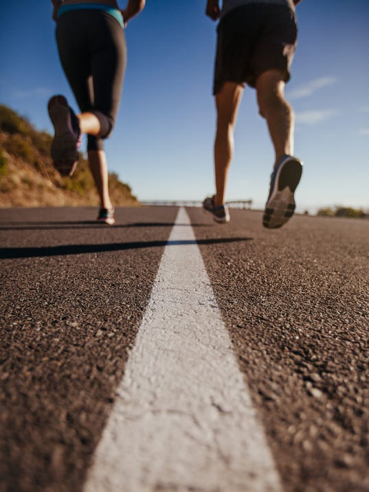 Athletes running on country road