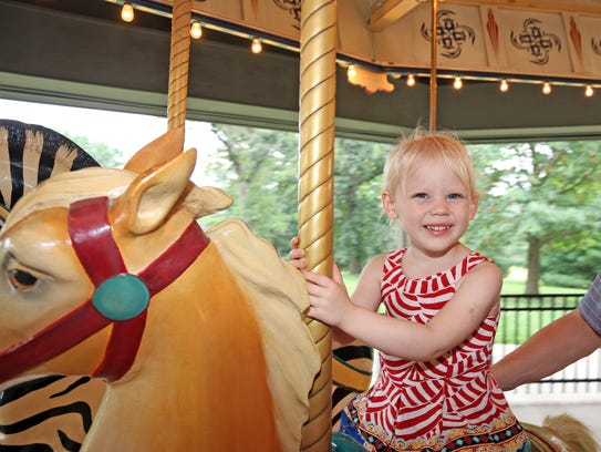 Zoey Vorria, 2, of Clive rides the Heritage Carousel at Union Park in Des Moines.