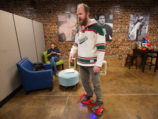 Mark Trusty, director of franchise development, scoots across the Hurts Donut corporate office on a hoverboard  as Tim Clegg, fonder and CEO, checks his cellphone on Monday, November 28, 2016.