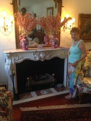 Gloria Hearn poses by a gas fireplace with an elaborately carved marble mantlepiece topped by a large, ornate mirror in the living room at Myrtlewood.
