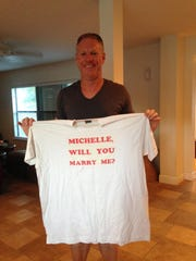 Michael Higgins holds up the t-shirt he made to propose to his wife. He was much larger back then.