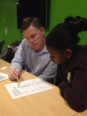 Mike Smith, a volunteer at the Boys & Girls Clubs of Rochester, tutors Giavanna Davis, 9, in math.