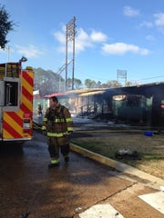 A fireman prepares to take a break while fighting a fire that destroyed the building that used to house the offices and clubhouse of the Alexandria Aces at Bringhurst Field.