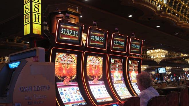 In this May 17, 2016 file photo, a gambler plays the slot machines at the Trump Taj Mahal casino in Atlantic City, N.J.
