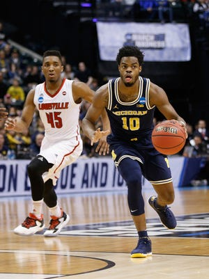 Michigan guard Derrick Walton Jr. drives against Donovan Mitchell of the Louisville Cardinals in the second round of the 2017 NCAA tournament at Bankers Life Fieldhouse on Saturday, March 19 in Indianapolis.
