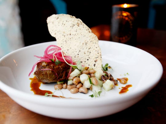 Zambra's vindaloo braised pork cheek, served with a small salad of black-eyed peas, cucumber and pickled onion.