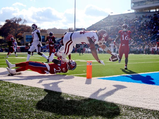 Oklahoma running back Rodney Anderson (24) dives into the end zone over Kansas safety Tyrone Miller Jr. (22) during an NCAA college football game at Memorial Stadium in Lawrence, Kan., Saturday, Nov. 18, 2017. Ian Maule/Tulsa World via AP)