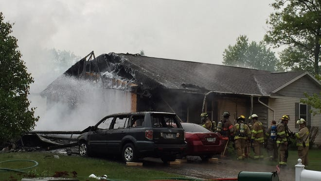 Firefighters spray the remains of a garage still smoking after a fire Tuesday at a home on Breezewood Court in Plover.