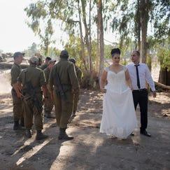 Israeli couple, Noga and Moshiko Siho, kiss after they have their wedding photos taken in an army staging area on the Israeli Gaza border, near Kibbutz Yad Mordechai, Israel, on Aug. 27.