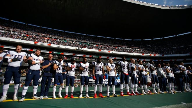 New England Patriots players stand during the national anthem before an NFL football game against the Oakland Raiders, Sunday, Nov. 19, 2017, in Mexico City.