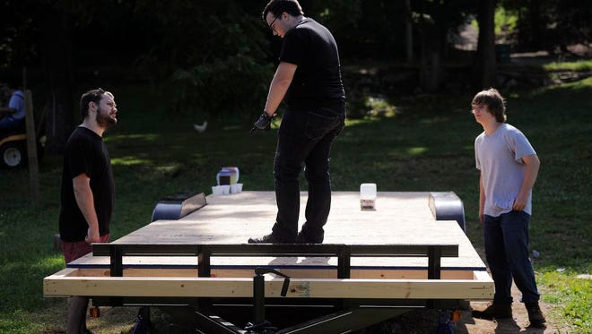 Stephen Lewis, Zach Hornsby and Jake Lewis (left to right) work on a trailer which will be a Tiny House Zach Hornsby and Stephen Lewis are building in Maukport, Indiana. Tiny homes are a post-Recession phenomenon, costing upwards of $10,000, with loft beds and micro appliances; a way to have no mortgage and live for less. June 6, 2014. By David Lee Hartlage, Special to the C-J.