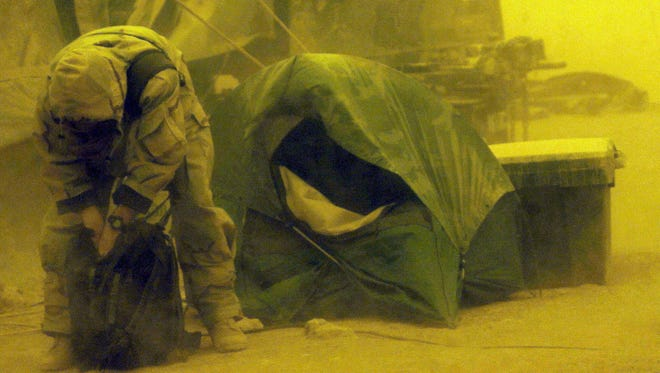 Operations officer Major Bill Gayler of Monticello, GA, tries to secure his gear during a ferocious sand storm at 101st Airborne Aviation Brigade's Forward Ammo and Refuel Point March 26, 2003, in the southern Iraqi desert. A blizzard of choking dust kept the 101st Airborne Division's fleet of more than 270 attack helicopters out of the battle for Iraq for the second day.