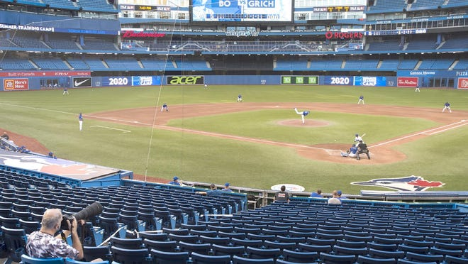 A photographer covers the game in an empty stadium during Friday's intrasquad game in Toronto.