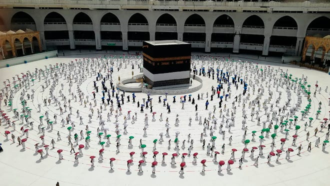 Hundreds of Muslim pilgrims circle the Kaaba, the cubic building at the Grand Mosque, as they observe social distancing to protect themselves against the coronavirus, July 29 in the Muslim holy city of Mecca, Saudi Arabia. During the first rites of hajj, Muslims circle the Kaaba counter-clockwise seven times while reciting supplications to God, then walk between two hills where Ibrahim's wife, Hagar, is believed to have run as she searched for water for her dying son before God brought forth a well that runs to this day.