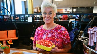 Food Network star Anne Burrell shows off some of her creations for an all-Cheetos menu for a three-day pop-up restaurant, during a press preview, Tuesday Aug. 15, 2017, in New York. Menu includes, Cheetos meatballs, Cheetos crusted fried pickles, Cheetos tacos, Mac n' Cheetos and Cheetos cheesecake. (AP Photo/Bebeto Matthews)