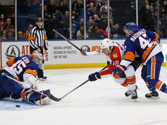 New York Islanders defenseman Andrew MacDonald, right, loses his stick while defending against Florida Panthers center Shawn Matthias (18) who eases the puck past Islanders goalie Anders Nilsson (45), of Sweden, for the go-ahead goal in the third period of an NHL hockey game in Uniondale, N.Y., Sunday, March 2, 2014. The Panthers defeated the Islanders 5-3. (AP Photo/Kathy Willens)