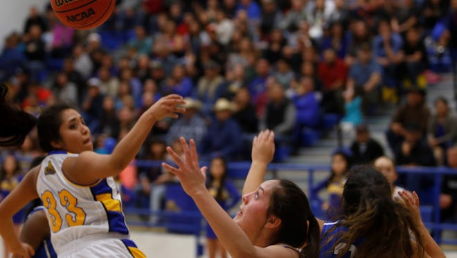 Bloomfield's Kara Watchman (33) drives the lane before dishing the ball off to teammate Destiny Walther (32) against Lovington on Friday at Bobcat Gym in Bloomfield.