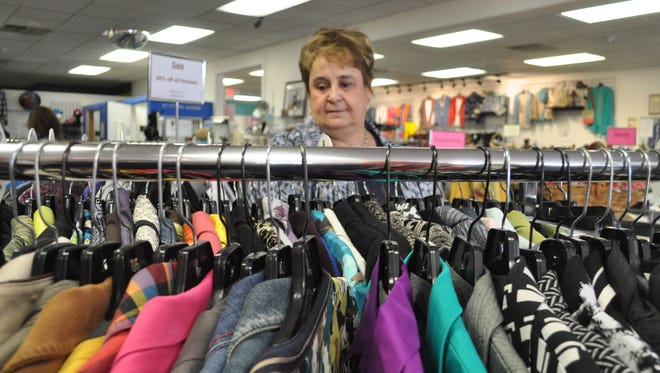 Nearly New Family Fashions owner Nina Colacino sorts women's blouses in her consignment store at 6803 N. Green Bay Ave.